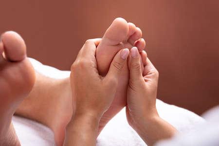 Close-up de la mano del terapeuta dando masaje de pies al hombre