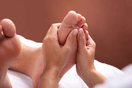 Close-up Of Therapist Hand Giving Foot Massage To Man Stockfoto