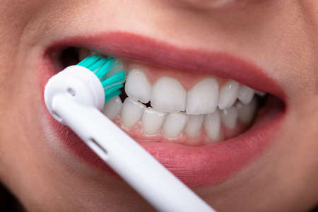 Close-up Of A Woman's Hand Brushing Teeth With Electric Toothbrush Zdjęcie Seryjne - 113242294