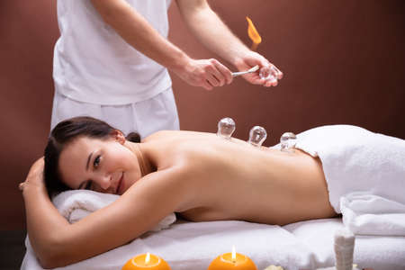 Male Therapist Giving Cupping Therapy To Young Woman In Spa Stock Photo