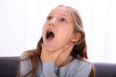 Porträt eines Mädchens, das nicht atmen kann und auf den Hals drückt