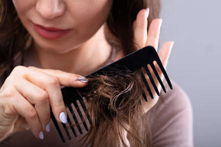 Close-up Of A Woman's Hand Combing Her Hair With Comb