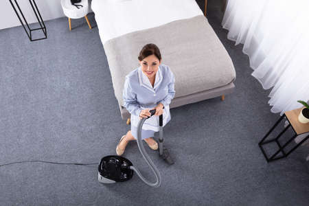 Happy Young Housekeeper Cleaning Carpet With Vacuum Cleaner In Hotel Room Banque d'images
