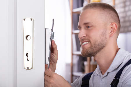 Close-up Of A Smiling Young Man Fixing Door Lock In House Standard-Bild - 113242566