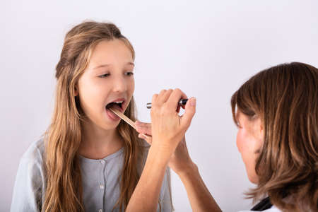 Close-up Of Doctor Checking Girl's Sore Throat With Tongue Depressor