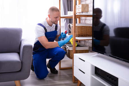 Smiling Male Janitor In Uniform Wiping Wooden Shelf