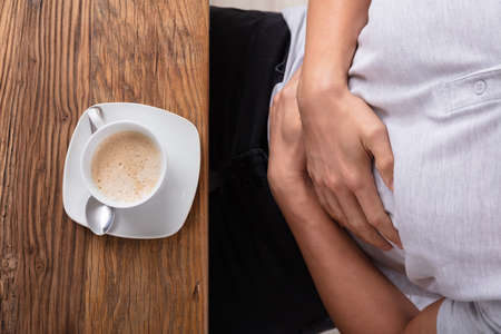 Man Suffering From Stomach Pain With Cup Of Coffee On Wooden Desk