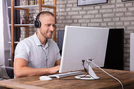 Smiling Young Man Using Headphone While Working On Computer Over Wooden Desk Фото со стока