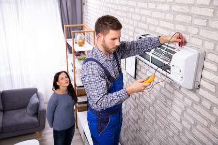 Young Woman Looking At Technician Examining Air Conditioner With Digital Multimeter Фото со стока