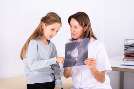 Close-up Of Girl Looking At Mature Female Doctor Holding Bone X-ray
