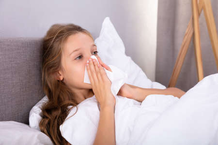 Girl Suffering From Cold Blowing Her Nose With Handkerchief On Bed