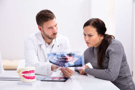 Young Male Dentist Showing Teeth X-ray To Female Patient In Clinic