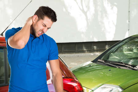 Young Man Suffering From Neck Pain Standing In Front Of Parked Cars Фото со стока