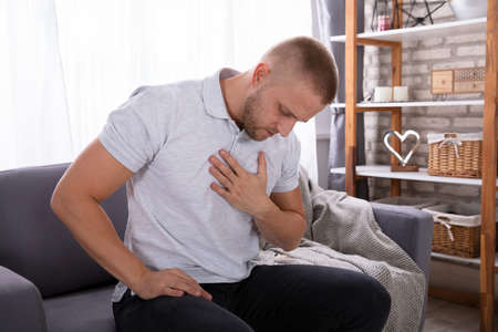 Man Touching His Chest While Suffering From Pain Фото со стока