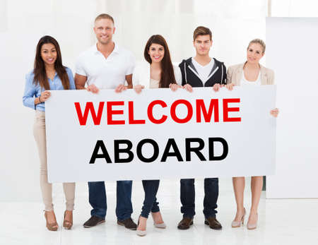 Group Of Happy People Standing Together With Welcome Aboard Placard Фото со стока