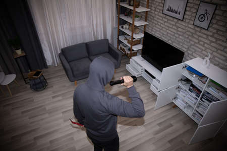 Thief With Flashlight Looking At Files In Shelf