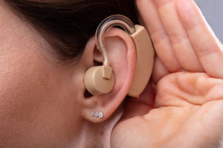 Woman Wearing Hearing Aid In Ear Listening For A Quiet Sound Фото со стока