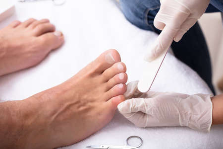 High Angle View Of Beautician Filling Mans Nail In Salon