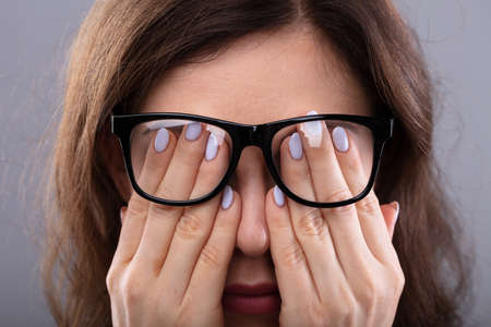 Close-up Of A Young Woman With Spectacles Covering Her Eyes