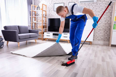 Young Male Janitor In Uniform Removing Dirt Under The Carpet Фото со стока