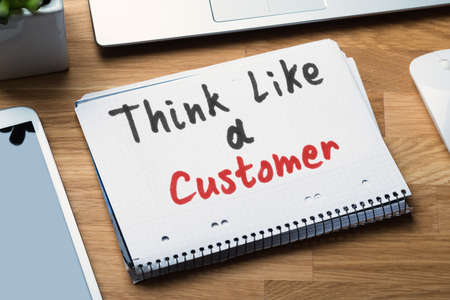 Think Like A Customer Text Written On Spiral Notepad With Electronic Gadgets On Desk Фото со стока