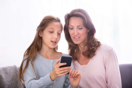 Portrait Of Mature Mother With Her Daughter Using Cellphone