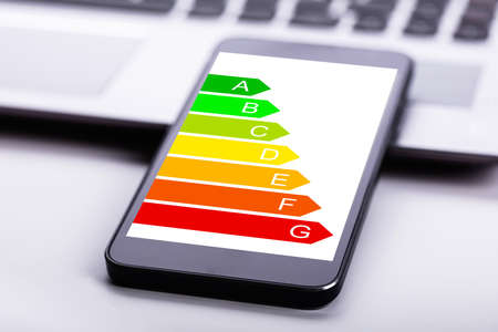 Close-up Of Laptop And Mobile Phone With Energy Efficiency Chart On Screen Over Desk