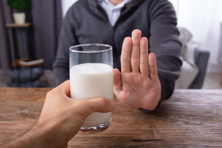 Close-up Of A Man Refusing Glass Of Milk Offered By Person Over Wooden Desk
