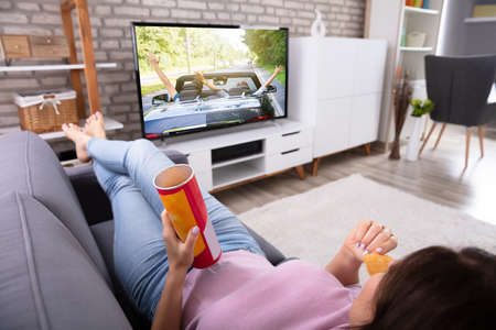 Woman Relaxing On Sofa Eating Potato Chips While Watching Television At Home