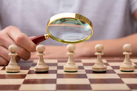 Close-up Of A Mans Hand Holding Magnifying Glass Over Pawn Chess Piece Stok Fotoğraf
