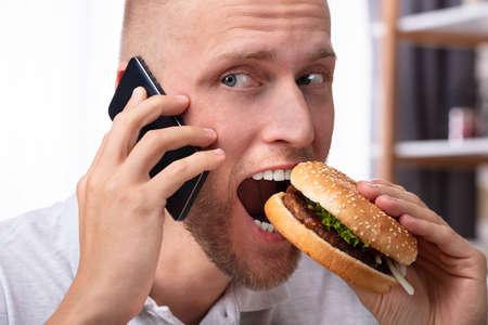 Portrait Of A Young Man Talking On Mobile Phone While Eating Burger