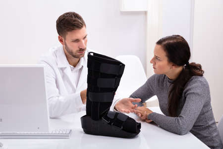 Doctor And Female Patient Sitting In Clinic With Walking Brace On Desk