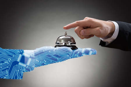 Businesspersons Hand Ringing Service Bell Held By Digital Generated Human Hand On Grey Background Stock Photo