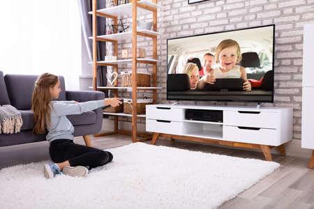 Mädchen sitzt auf dem Teppich und schaut zu Hause fern Television
