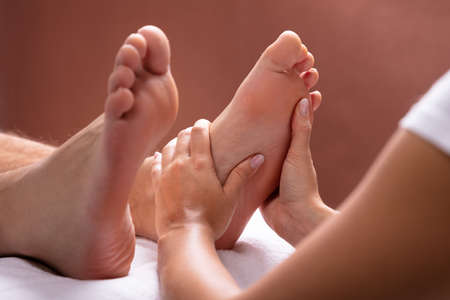 Close-up Of Therapist Hand Giving Foot Massage To Man Фото со стока