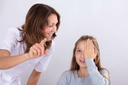 Smiling Female Optometrist Assisting Girl While Checking Eyesight In Clinic Foto de archivo