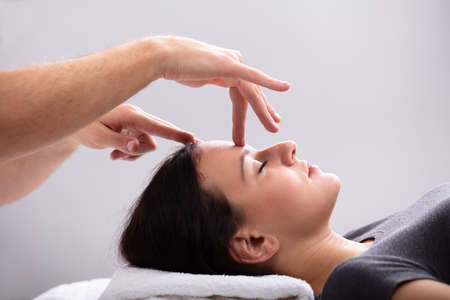 Close-up Of A Young Woman Receiving Reiki Treatment By Therapist Фото со стока