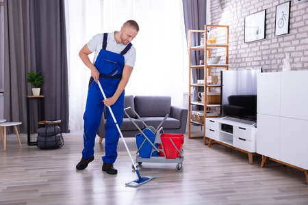 Smiling Male Janitor Cleaning Floor With Mop In Living Room