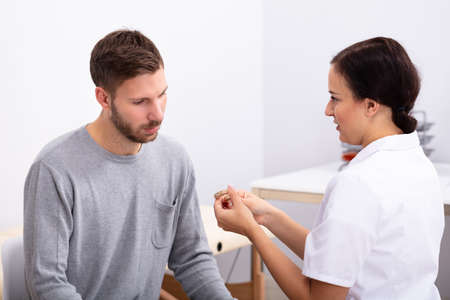 Young Male Patient Looking At Female Doctor Holding Hearing Aid In Clinic Фото со стока