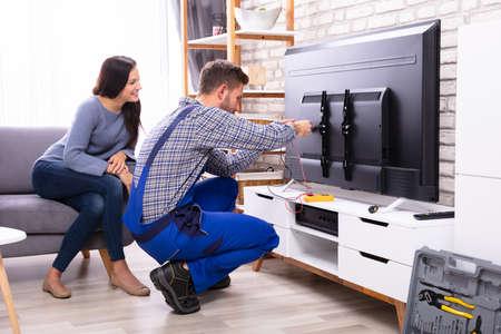 Woman Sitting On Sofa Near Male Technician Repairing Television Фото со стока