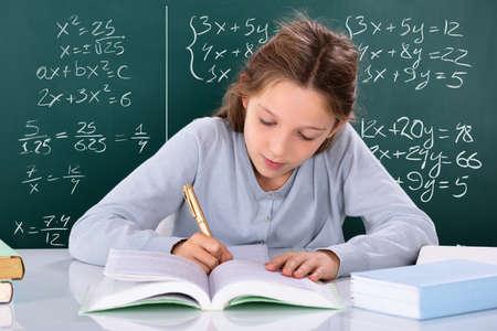 Portrait Of A Girl Doing Study In Front Of Green Chalkboard Фото со стока