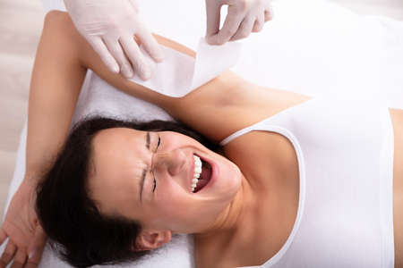 Elevated View Of Young Woman Screaming While Removing Armpit Hair With Wax Strip