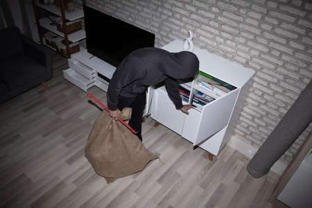 Elevated View Of Thief With Crowbar And Sack Stealing File From Shelf
