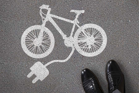 Close-up Of Persons Feet Standing Next To Painted Electric Bicycle On Asphalt