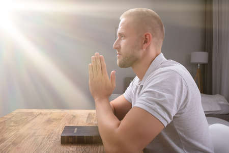 Side View Of A Young Man Praying With Bible Over Wooden Desk At Home