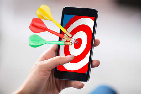Close-up Of A Persons Hand Holding Cellphone With Colorful Darts On Target