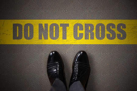 Persons Feet Standing Near Yellow Line With Do Not Cross Text On Asphalt Фото со стока