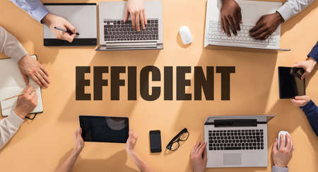 Efficient Word Surrounded With Businesspeople Using Electronic Gadgets On Table Фото со стока