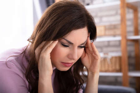 Close-up Of A Beautiful Young Woman Suffering From Headache