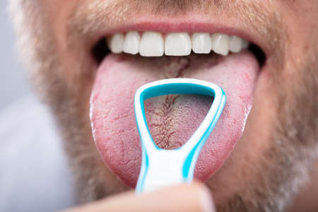 Close-up Of A Man Cleaning His Tongue With Cleaner